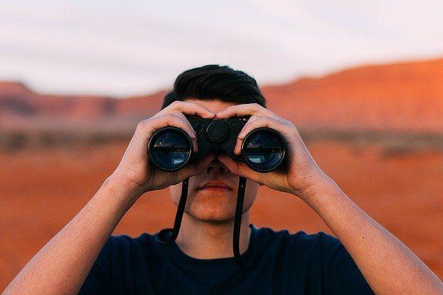 uomo con binocolo in mano