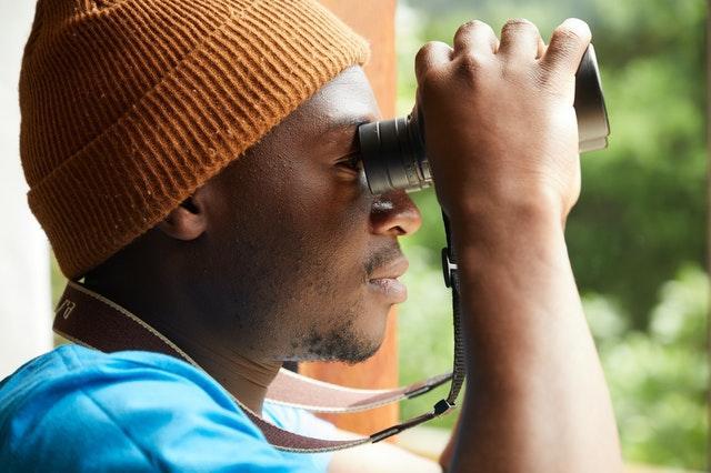 uomo di profilo con binocolo