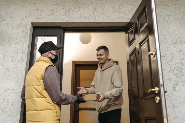uomo apre la porta al corriere