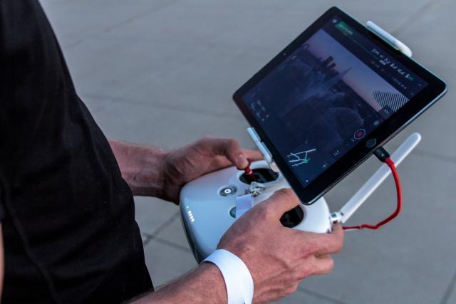 un uomo tiene tra le mani un dispositivo di controllo dei droni